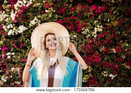 Smiling Blonde Woman in beachwear and hat which posing near the flower bush and looking up