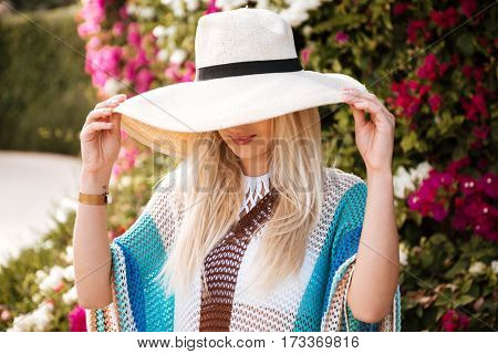 Close-up view of Woman in hat and beachwear which posing near the flower bush