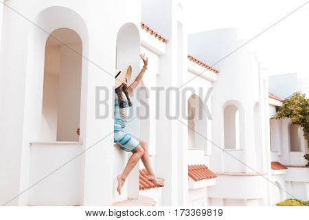 Side view of Brunette woman in beachwear which sits on the edge of balcony and waving away
