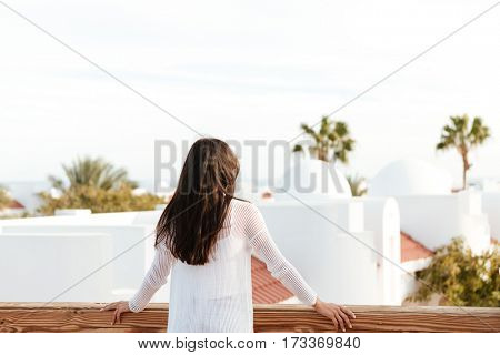 Back view of Brunette woman in white clothes which standing on roof of building and looking away