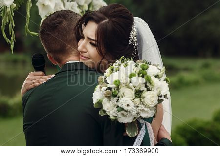 Gorgeous Emotional Bride Crying While Hugging Groom And Taking Vows On Aisle At Lake At Wedding Outd