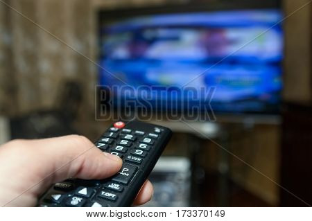 Hand holding remote control in front and operating TV on background