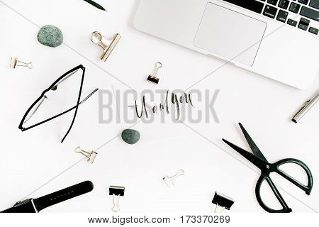 White office desk workspace with words thank you and supplies. Laptop scissors pen clips glasses and office supplies on white background. Flat lay top view.