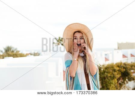 Shocked Blonde woman in beachwear which talking on phone and covering her mouth