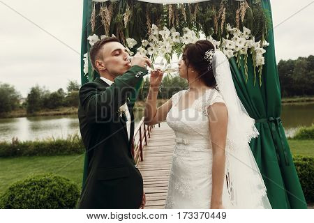 Happy Couple Of Newlyweds Drinking Champagne Outdoors Near White Flowers Garland At Wedding Aisle, L