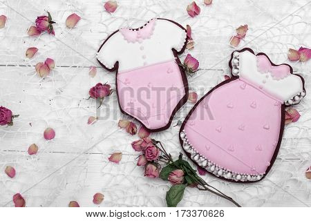 Cookies With Glaze In The Form Of Dress And Baby Body Withpetals Of Dried Roses. On White Wooden Sur