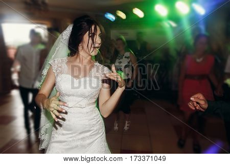 Beautiful Happy Smiling Bride In White Dress Dancing And Having Fun At Night Wedding Reception In Re