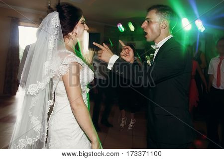 Happy Smiling Newlywed Couple, Handsome Groom And Beautiful Brunette Bride Dancing And Having Fun At
