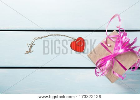 Gift box with nice pink ribbon and decorative heart with chain on blue wooden background. Free space for text.