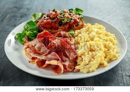 Morning Scrambled egg, bacon breakfast with beans in tomato sauce on toasted bread on white plate.