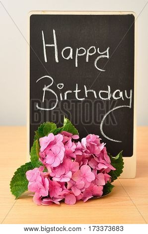 A blackboard with a happy birthday message and hydrangeas