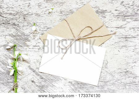 blank white greeting card and envelope with snowdrop flowers over rustic table with copy space. mock up