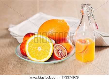 a bottle with a fresh juice from the oranges and blood oranges on a wooden surface