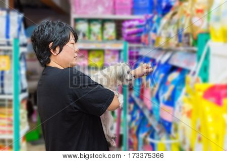 Many types of pet food (Dog Cat and other) on pet goods shelf in pet shop.