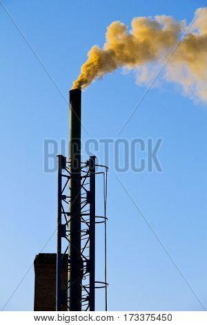 Dark smoke from the chimney against blue sky