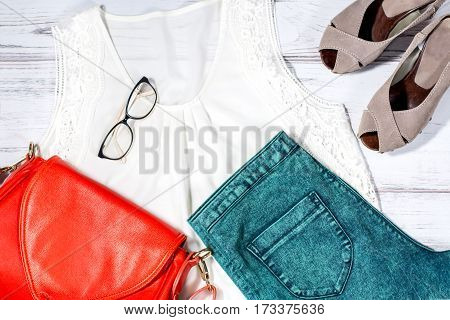 Woman clothes in romantic casual style - stylish dark green jeans, white chiffon top, suede shoes, bright red leather bag and glasses
