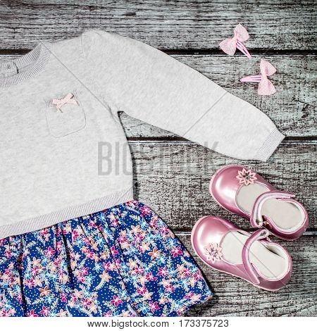 Baby girl stylish casual clothes - grey and blue dress with flower print, pink leather shoes, pink hair bows, on a rustic wooden background