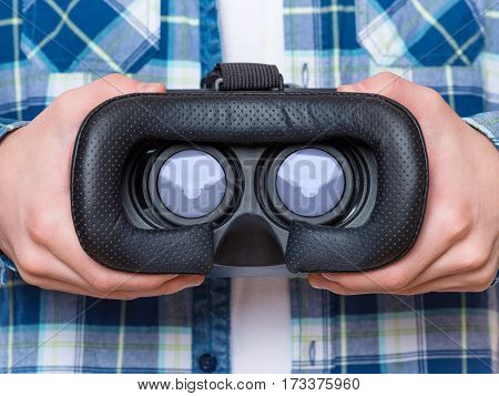 Close-up of hands with virtual reality VR goggles - experiencing 3D gadget technology - looking in VR.