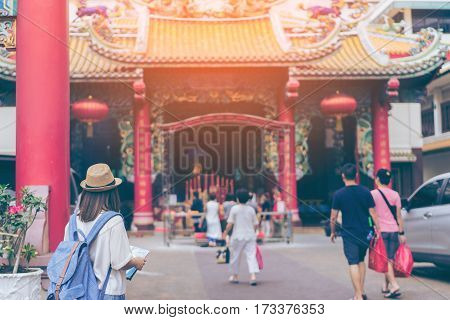 Young woman traveler with sky blue backpack and hat looking the map with chinese temple background from china town Bangkok. Traveling in Bangkok Thailand