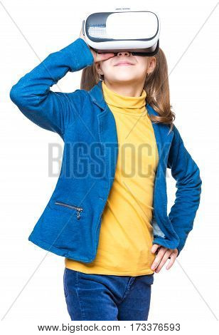 Happy little girl wearing virtual reality goggles watching movies or playing video games, isolated on white. Cheerful smiling kid looking in VR glasses. Funny child experiencing 3D gadget technology.