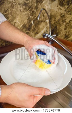 Man hands washing a sponge with foam the dishes at the kitchen