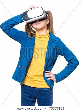 Thoughtful little girl wearing virtual reality goggles watching movies or playing video games, on white. Casual thinking kid looking in VR glasses. Emotional portrait of child experiencing 3D gadget technology.