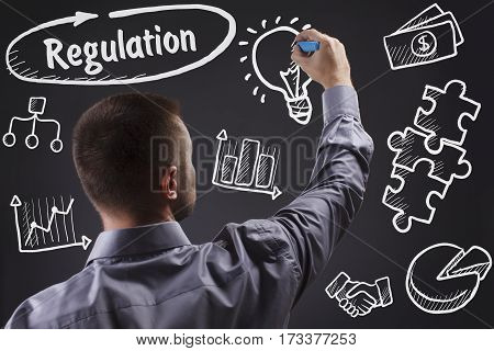 Technology, Internet, Business And Marketing. Young Business Man Writing Word: Regulation