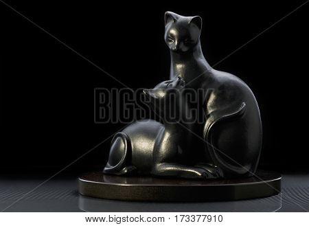 ceramic figurine two black cats on black background