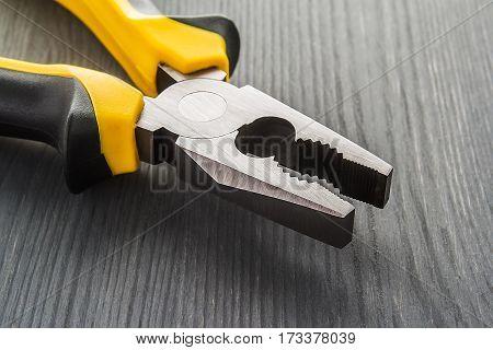 Pliers on a dark wooden table. electrician, orange,