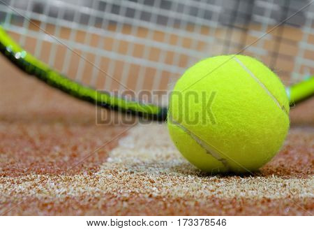 Tennis ball and racket on the court. Soft focus on tennis ball. Blurred background.