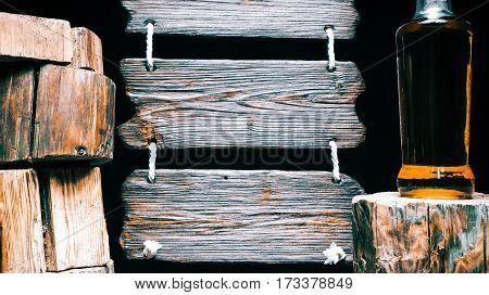 Whiskey or brandy bottle on wood stump. Other stumps in stack. Triple wood sign on the background. Isolated over black