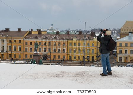 HELSINKI, FINLAND - FEBRUARY 14, 2013: Unidentified tourist takes photo at the central square of the city in Helsinki, Finland.