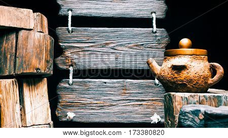 Clay teapot on wood stump. Other stumps in stack. Triple wood sign on the background. Isolated over black