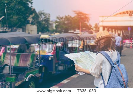 Young woman traveler with sky blue backpack and hat looking the map with tuk tuk Thailand background from china town Bangkok. Traveling in Bangkok Thailand