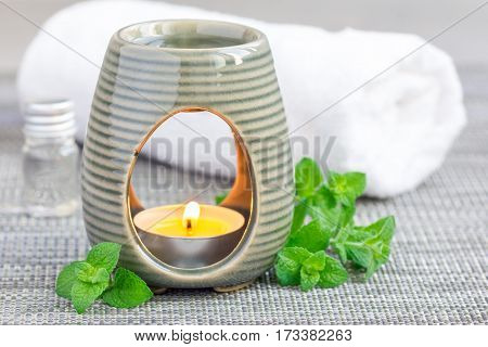 Peppermint essential oil in aroma lamp on gray mat with spa background horizontal