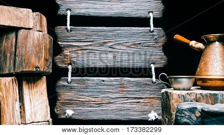 Coffee pot and cup on wood stump. Other stumps in stack. Triple wood sign on the background. Isolated over black