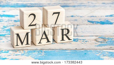 March 27th. Wooden cubes with date of 27 March on old blue wooden background.