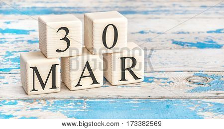 March 30th. Wooden cubes with date of 30 March on old blue wooden background.