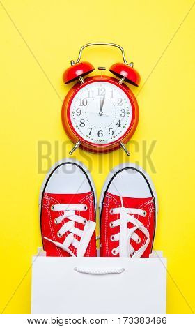 big red gumshoes in cool shopping bag and cute alarm clock on the wonderful yellow background poster