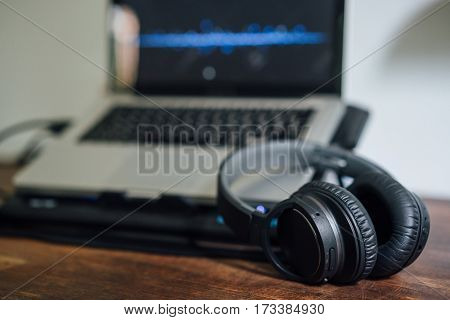 Laptop keyboard with wireless headphones for music.