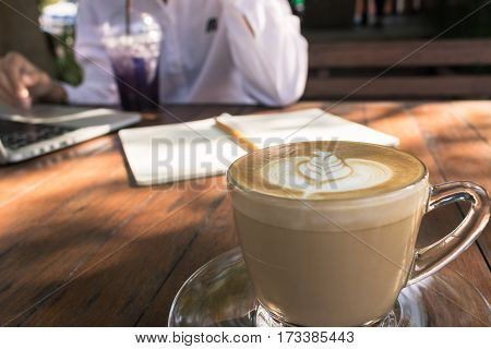 Close up coffee latte art and background business woman working outdoor in coffee shop vintage tone.