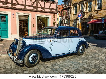 BAMBERG, GERMANY - Circa September, 2016: Old vintage car parked on the cobbled streets of the old town in Bamberg, Bavaria, Germany in a nostalgic urban scene