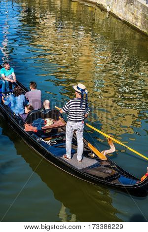 BAMBERG, GERMANY - Circa September, 2016: Overhead view of man in hat and striped shirt rowing gondola full of passengers