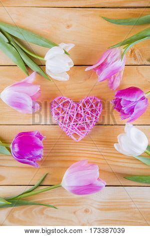 Bouquet Of Tender Pink Tulips With Wicker Heart On Light Wooden Background