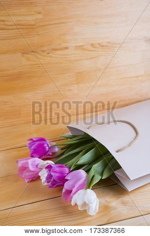 Bouquet Of Tender Pink Tulips In Creamy Shopping Bag On Wooden Background