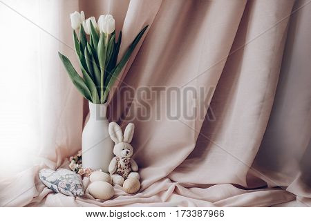 Stylish White Tulips In Minimalistic Vase On Background Of Beige Fabric And Wooden Eggs In Soft Ligh