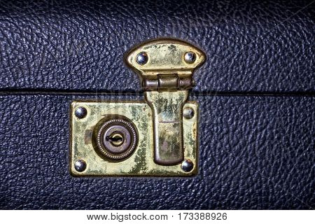 Lock golden color on an old suitcase made of black leather