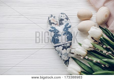 Stylish White Tulips Easter Eggs And Bunny Floral Heart On Rustic Wooden Background Top View. Happy
