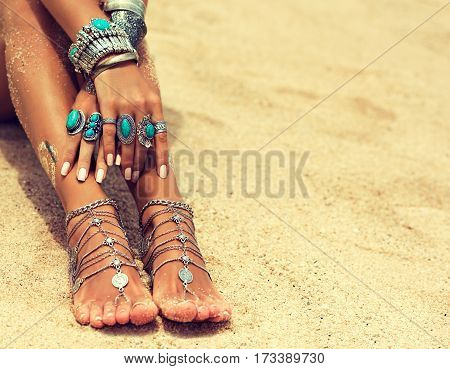 Woman  feet and hands In On Tropical Beach with sand , body parts  . Tanned girl  foot with silver jewelry,bracelets and rings with turquoise.