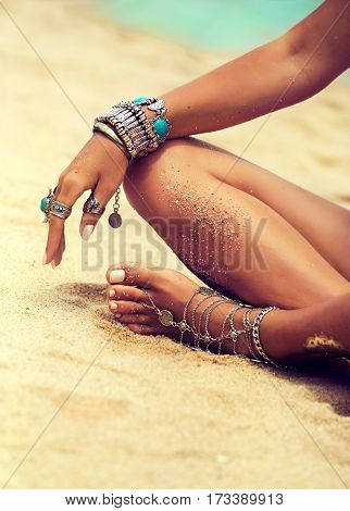 Woman In Relaxation On Tropical Beach with sand , body parts  . Tanned girl in Lotus position with silver jewelry,bracelets and rings with turquoise.